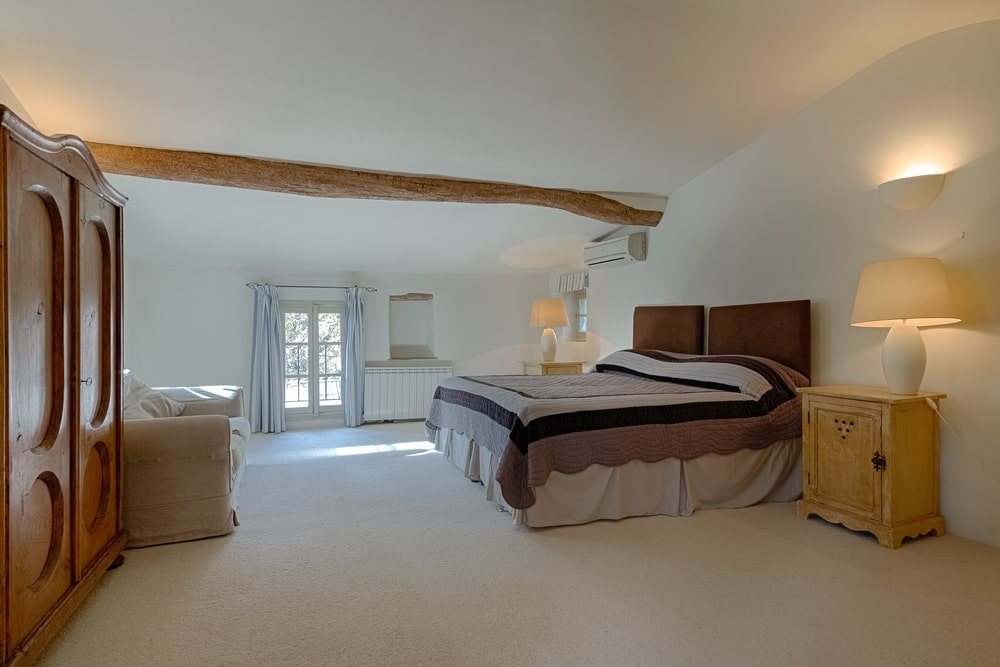 This bedroom has a bright white cove ceiling with a single exposed log beam. The bed has a dark brown cushioned headboard flanked by bedside drawers and table lamps. Image courtesy of Toptenrealestatedeals.com.