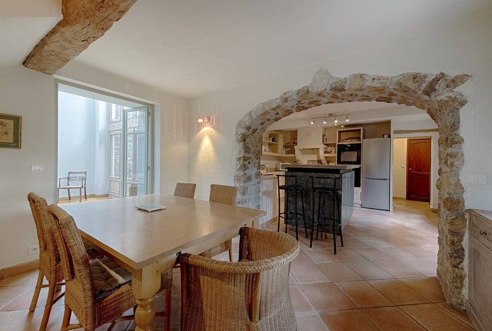 Just a few steps from the kitchen is this breakfast nook with a small square wooden dining table surrounded by woven wicker chairs. On the far side you can see the arched entryway for the kitchen. Image courtesy of Toptenrealestatedeals.com.