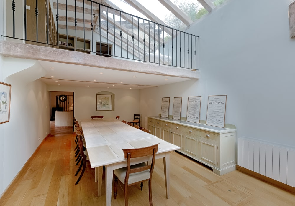 The dining room has a long white dining table that matches well with the walls. These are then contrasted by the wooden chairs and the hardwood flooring.Image courtesy of Toptenrealestatedeals.com.