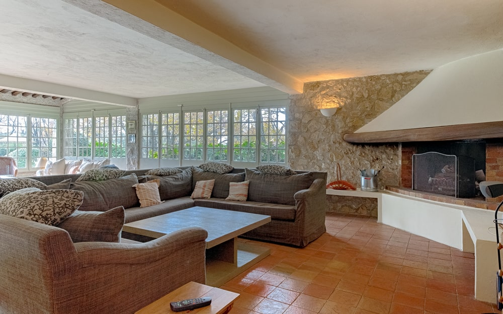 This is the family room with a large gray L-shaped sectional sofa and a wooden coffee table across from the fireplace at the corner. Image courtesy of Toptenrealestatedeals.com.