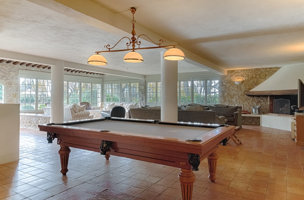 A few steps from the living room is this game area fitted with a large pool table topped with a row of pendant lights. Image courtesy of Toptenrealestatedeals.com.