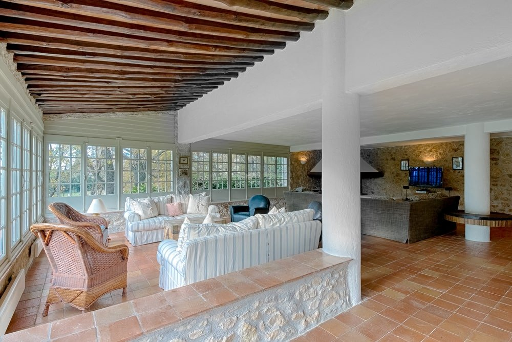 The living room has a pair of white sofas along with cushioned armchairs under an arched ceiling with exposed beams. Image courtesy of Toptenrealestatedeals.com.