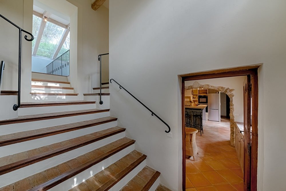This is a close look at the stairs that has wooden steps that stand out against the white walls with wall-mounted wrought-iron banisters. Image courtesy of Toptenrealestatedeals.com.