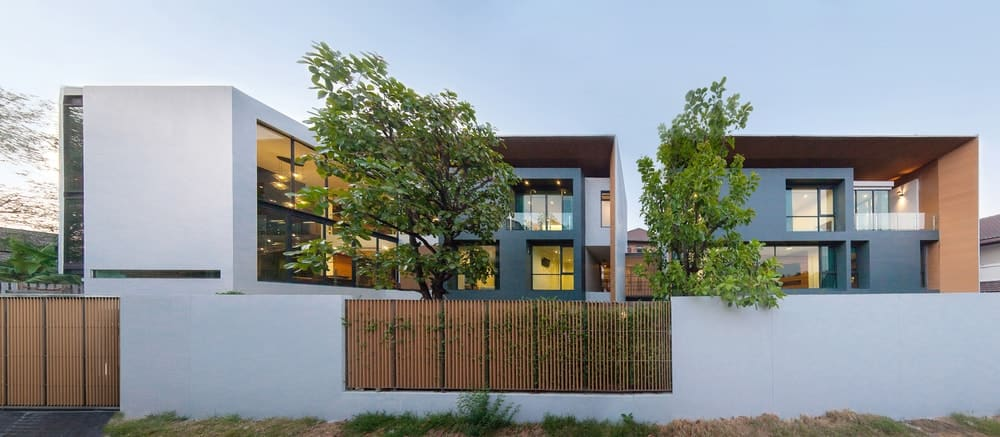 This is a look at the front of the house that has three large structures with a modern and bright aesthetic that has glass walls and white exteriors complemented by the wooden tones and the tall trees.