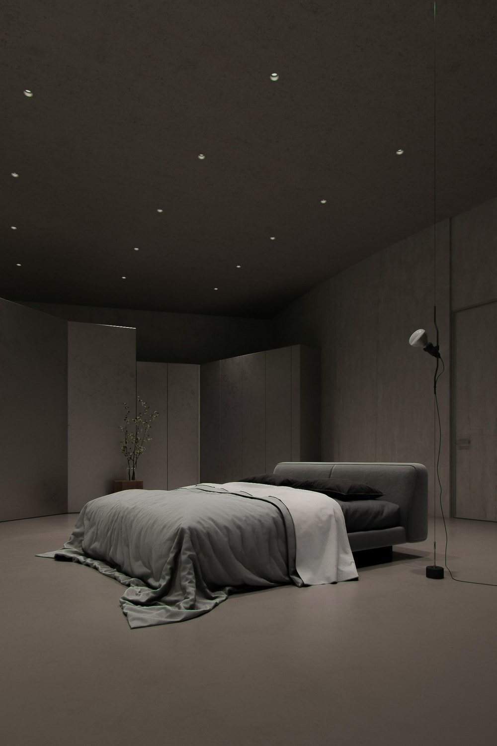 The gray cushioned bed of the bedroom is topped iwth a large tall ceiling that has small recessed lights.