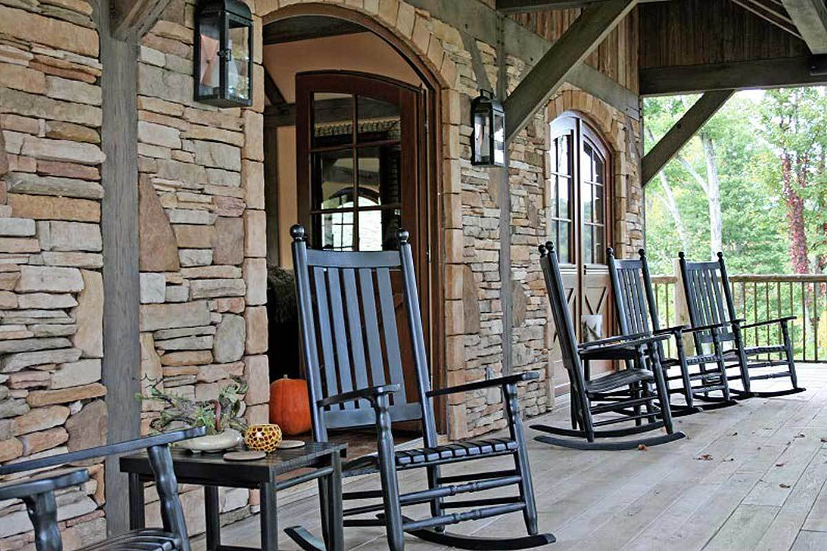 The covered porch is filled with dark wood rocking chairs and outdoor sconces mounted on the stone walls.