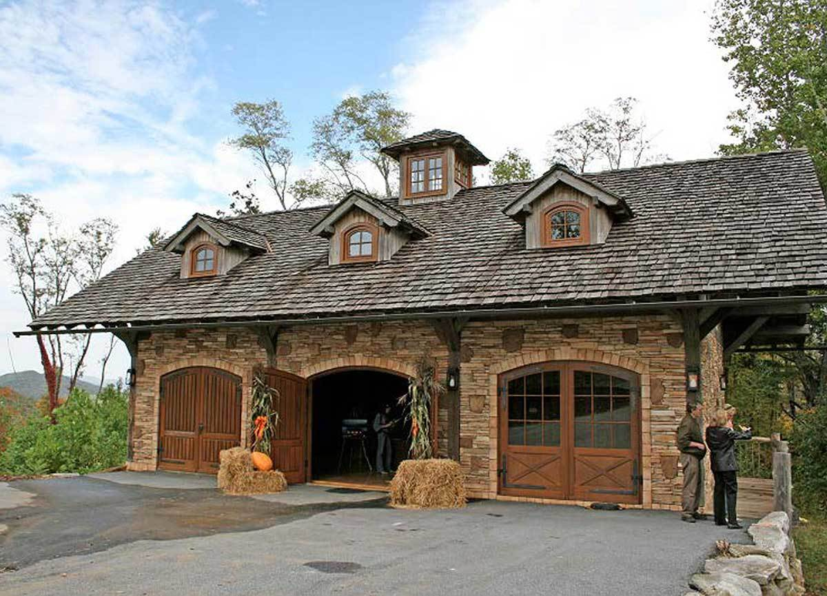 The home features stone walls, arched double doors, and dormer windows sitting on the gable roof.