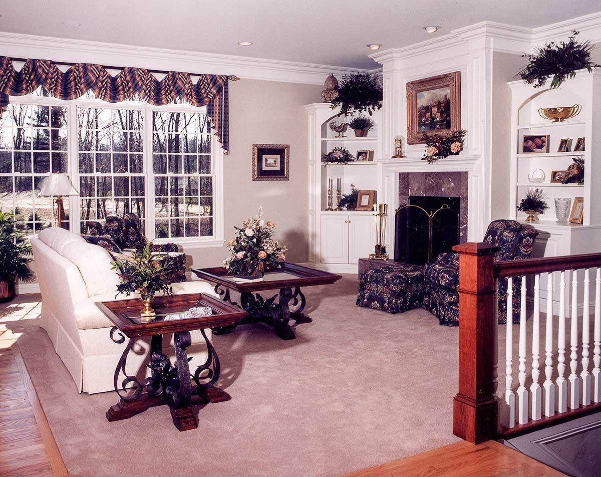 Living room with white sectional sofa, printed armchairs, ornate coffee tables, and a fireplace flanked by white built-ins.