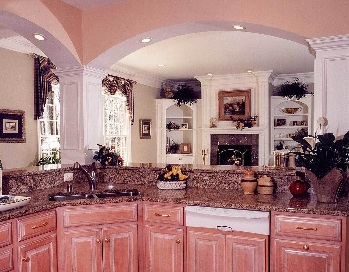 View of the living room from the kitchen with a curved peninsula framed with open arches.