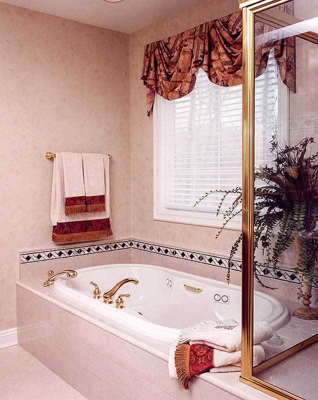 The primary bathroom features a deep soaking tub fixed under the white framed window.