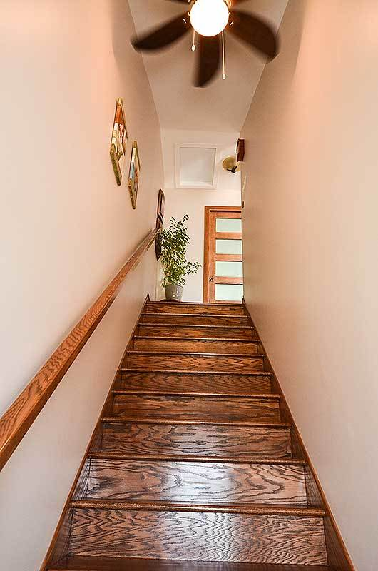 A steep staircase from the garage leading to the living room.