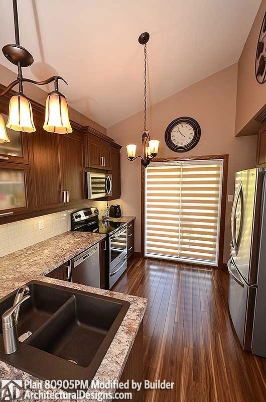 The kitchen is equipped with granite countertops, slate appliances, double bowl sink, and natural wood cabinets.