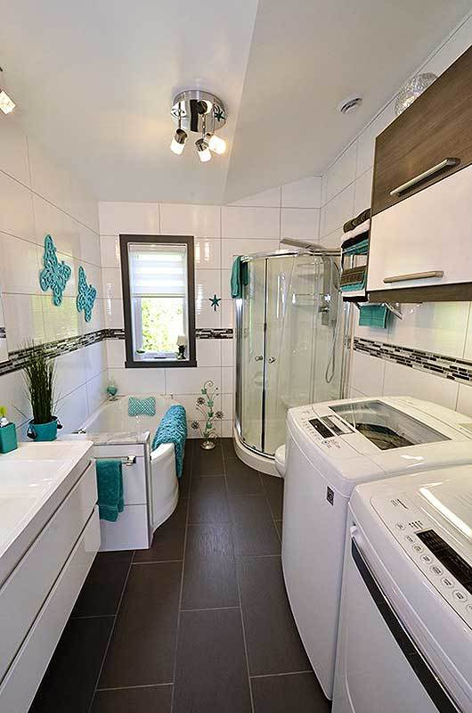 The bathroom is filled with a shower area, drop-in bathtub, floating vanity, and white top-load appliances.