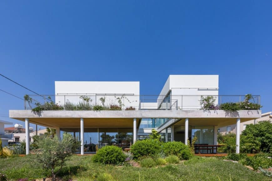 This is a bright and white house with two large structures connected by the glass walls of the ground floor and the large balcony of the second floor adorned by the landscape on both levels.