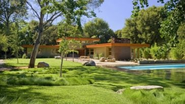This home has a large grass lawn at the back by the pool area. You can also see here the background of tall trees that complements the earthy tone of the house.