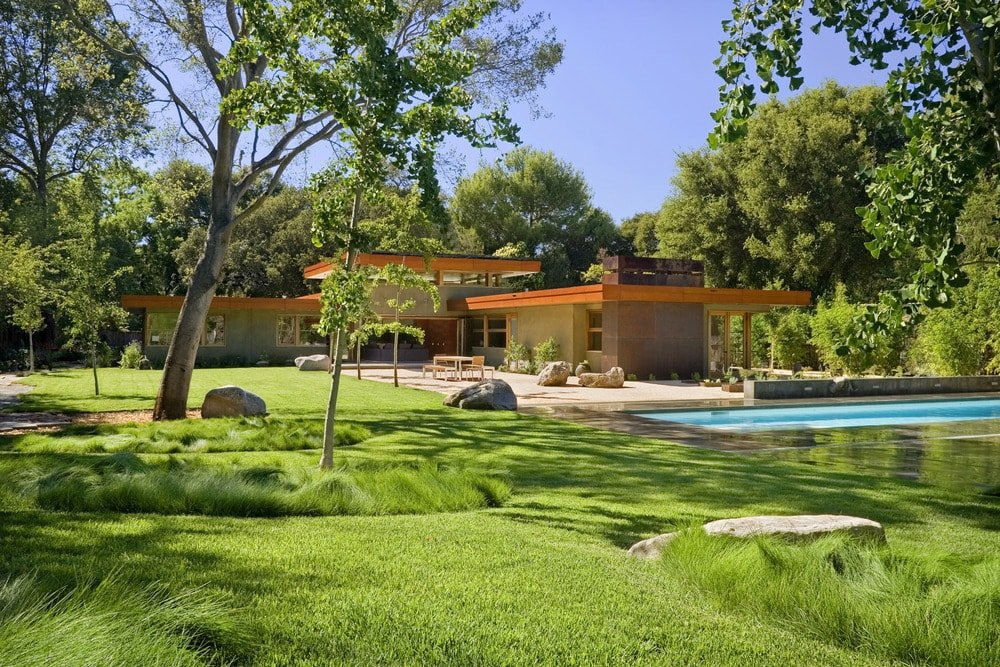 This is a look at the back of the house with earthy tones to its exterior walls accented with bright orange roof that works well with the surrounding green landscape to complement the exteriors.