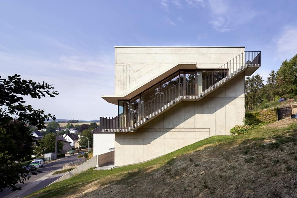 This is a side view of the house with concrete exterior walls adorned with a staircase on the side that has glass walls on one side and railings on the other that leads all the way to the rooftop level.