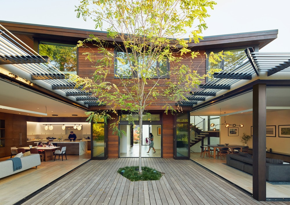 In the middle of the two sections of the house with open walls is a wooden deck area with a tall tree planted in the middle. This pairs well with the dark wooden exterior wall of the house.