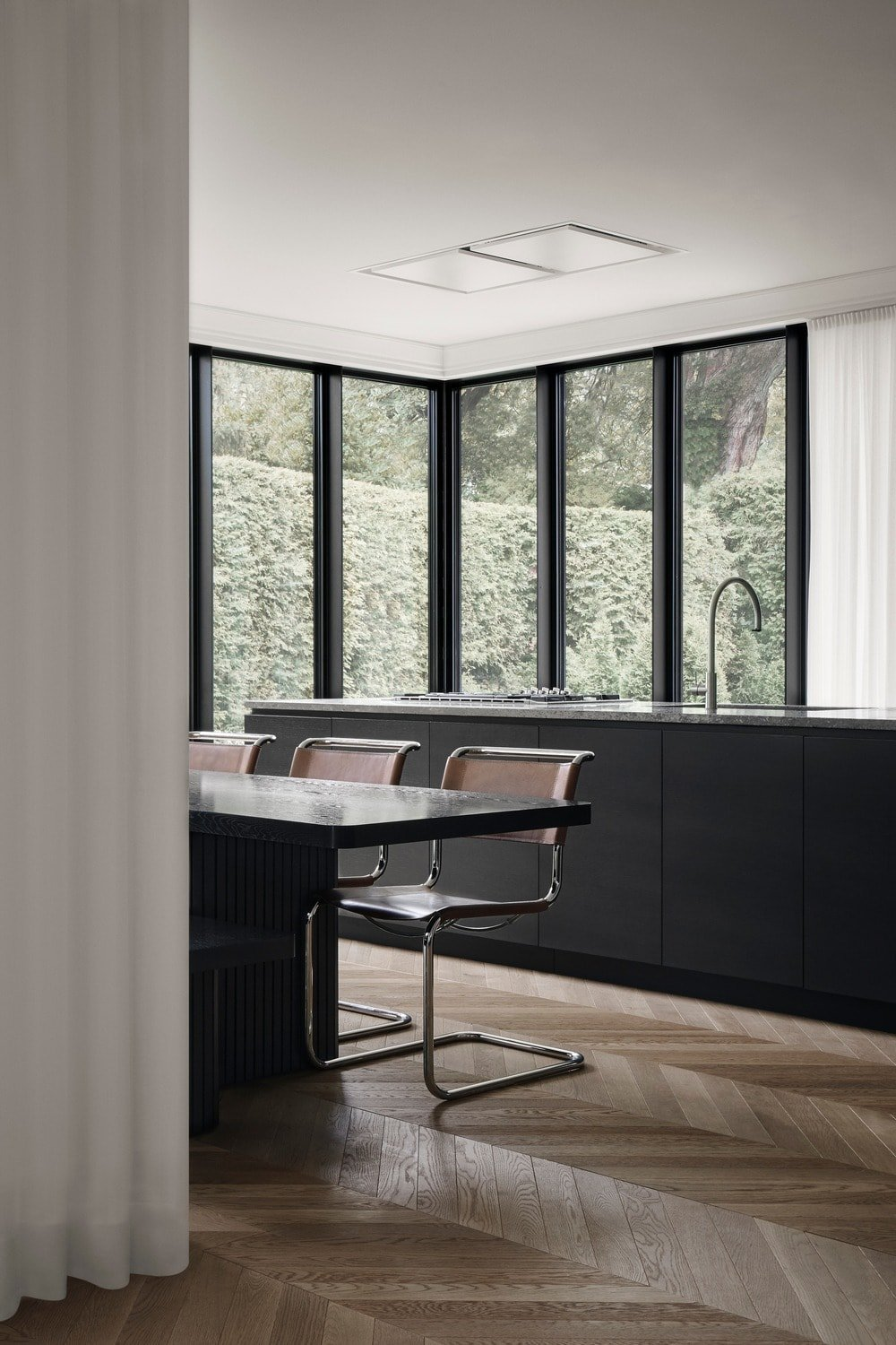 The dining area has a black dining table surrounded by modern chairs and a wooden bench.