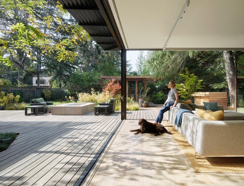 The whole area of the living room and dining are open to the backyard and the middle wooden deck area. This brings in an abundance of natural light and colorful landscape background.