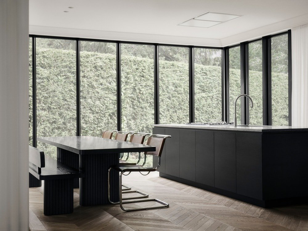 This is a look at the dining area and the kitchen beside it. Both of these sections have black elements that match the frames of the glass walls.