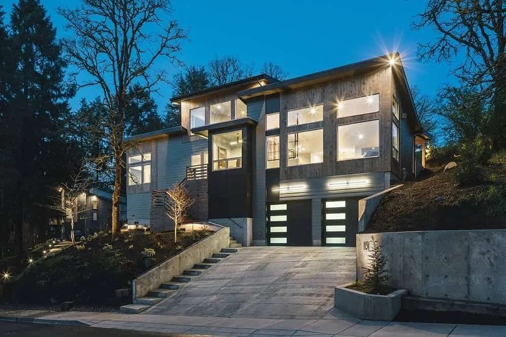 This is a look at the front of the house with an inclined driveway leading to the garage doors that pair well with the large glass walls of the house that give glimpses of the interiors as well as glow warmly to complement the gray exterior walls.