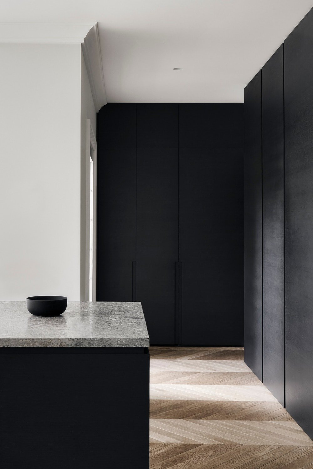The black kitchen island matches well with the rest of the kitchen's cabinetry paired with black appliances.