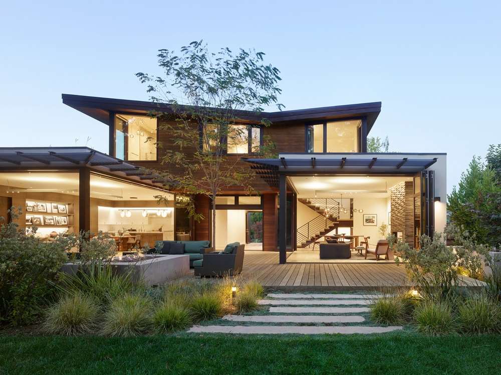 This is a look at the back of the house from the vantage of the backyard lawn. You can see here the open walls and large glass walls of the house the glow warmly from the interior lights.