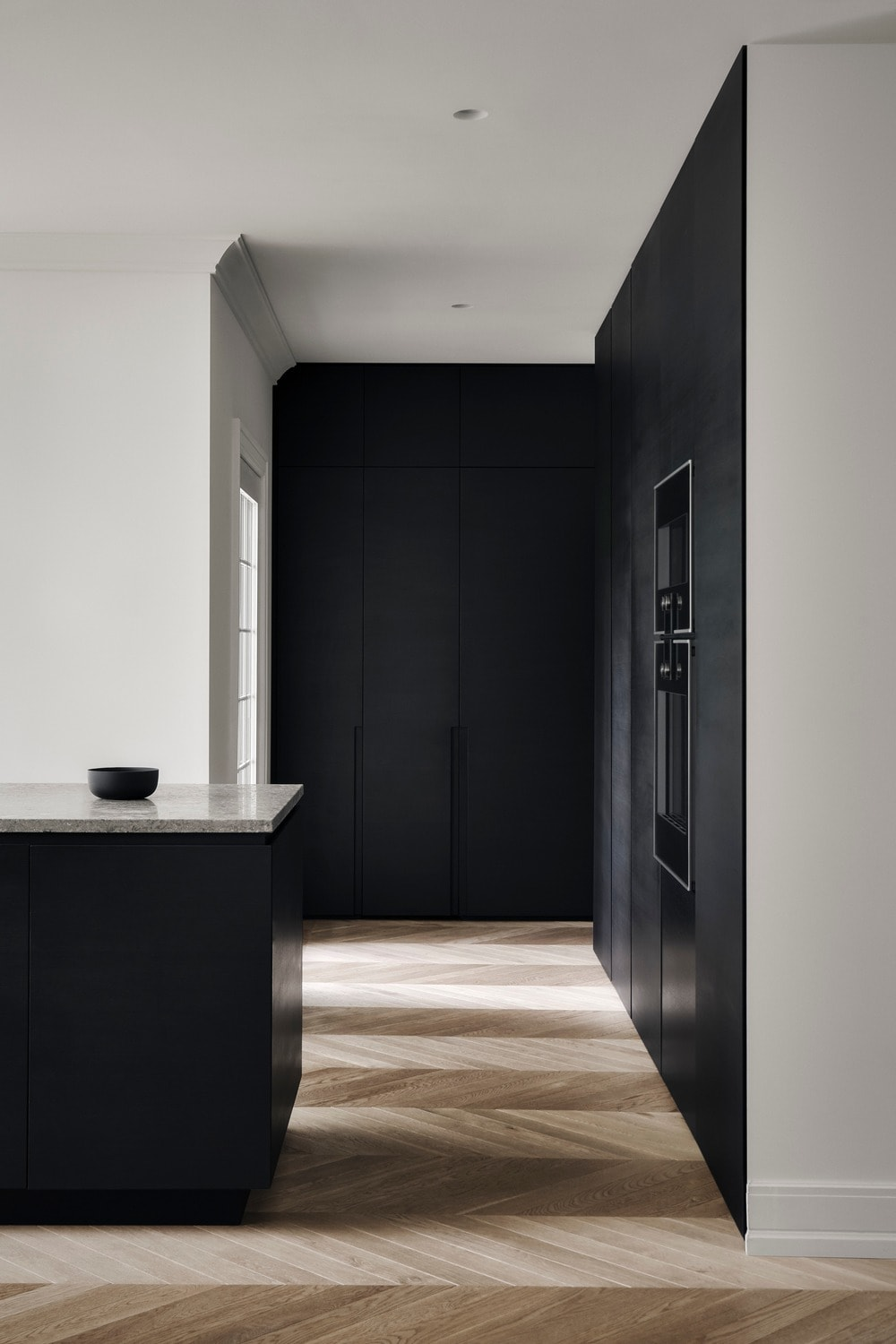 The kitchen has a large black kitchen island that is contrasted by the white marble countertop.