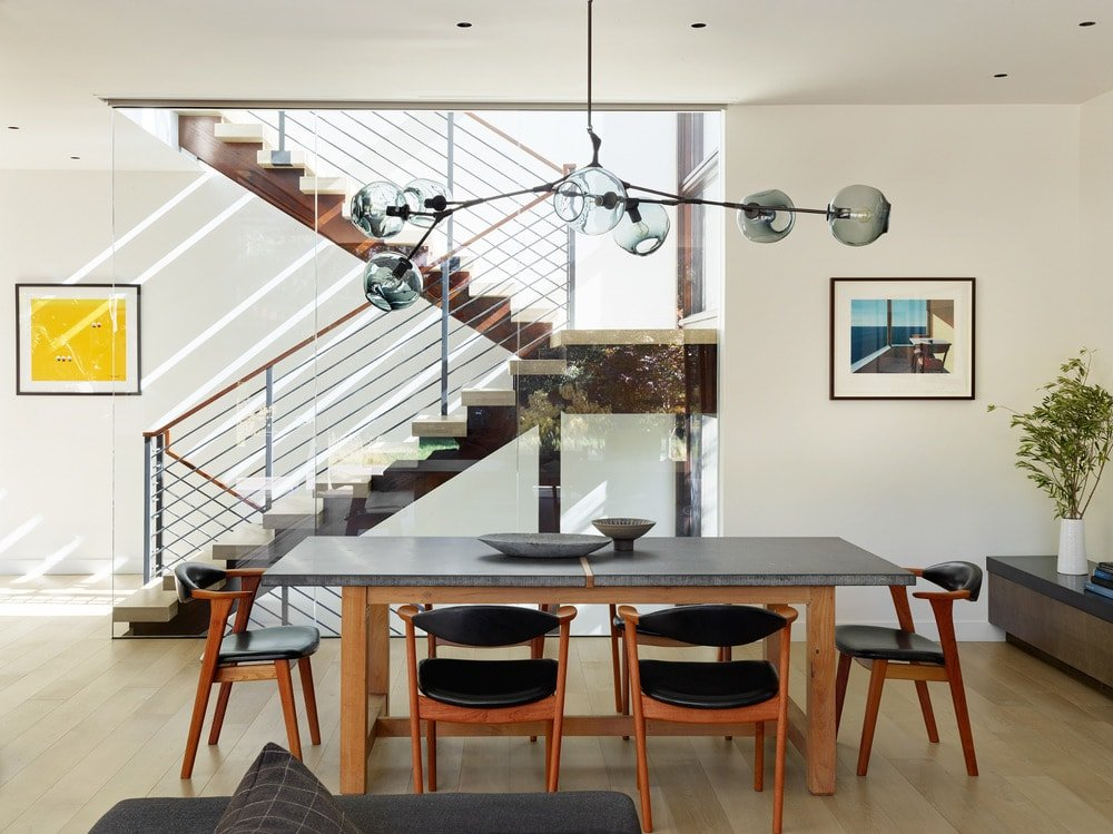 This is the dining area that has a wooden dining set under a decorative lighting.