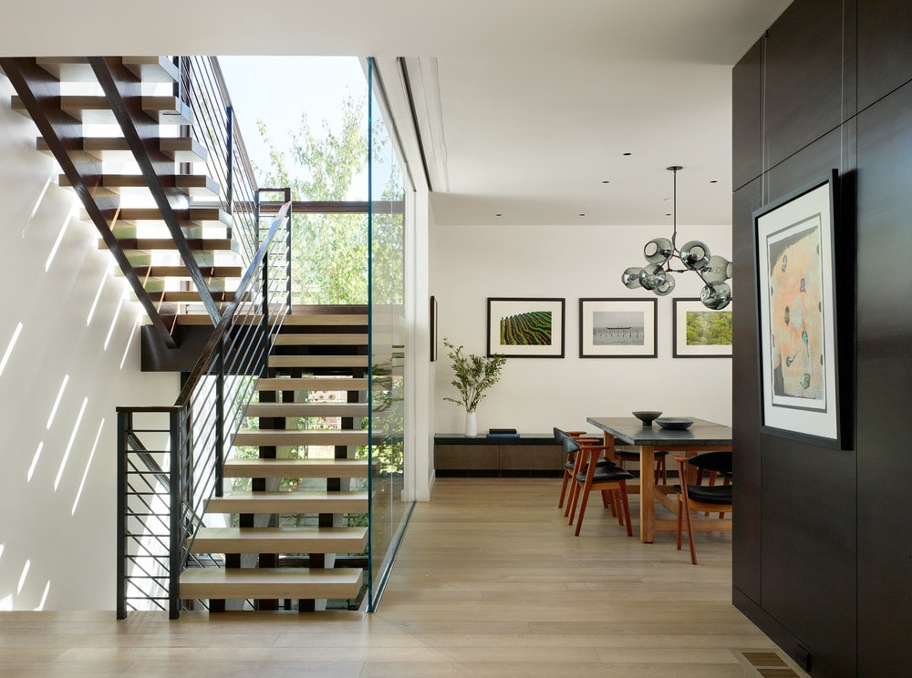 A few steps from the dining area is the stairs that is adorned with glass walls and wrought-iron railings.