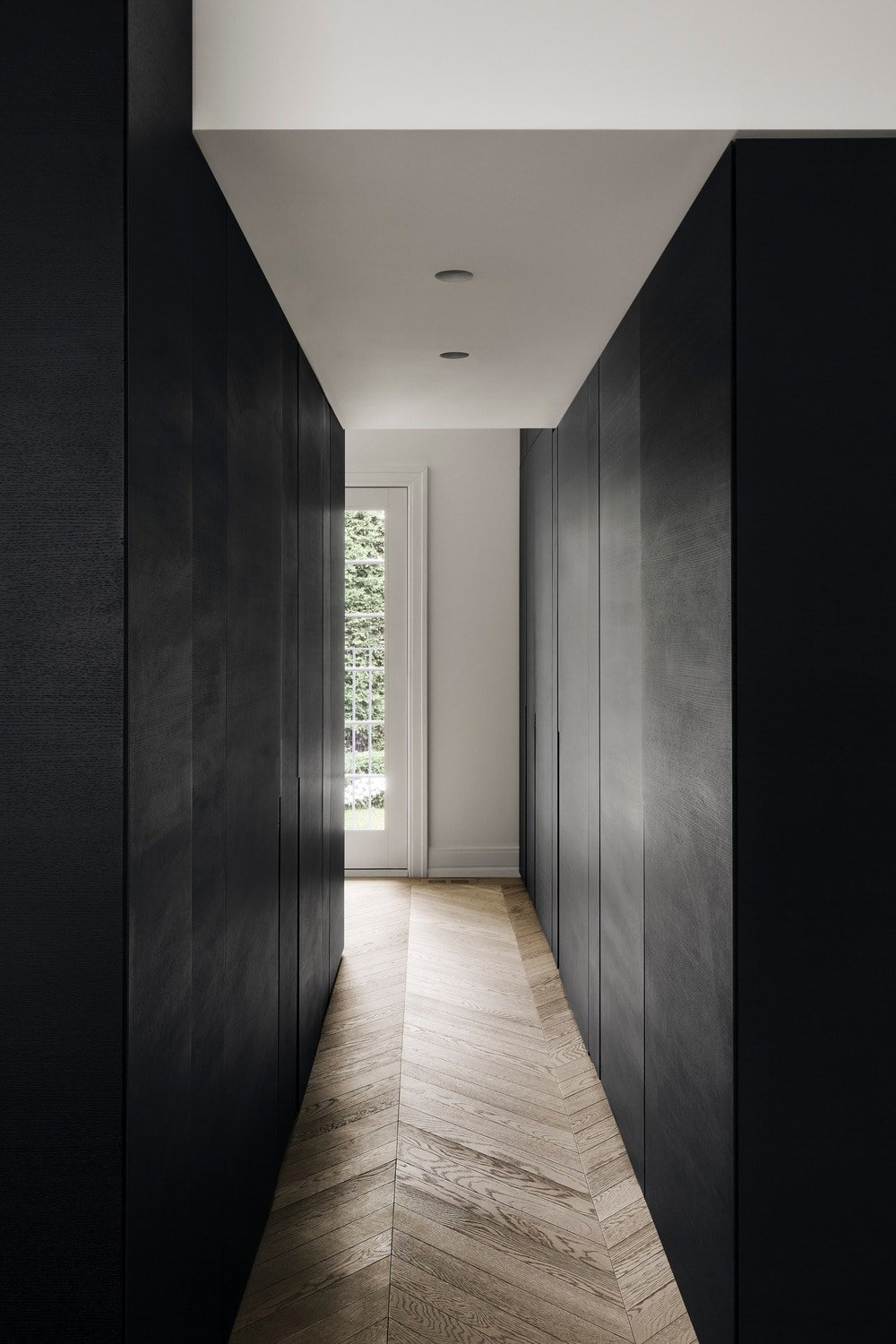 This is a hallway with black modern cabinets on either side to complement the herringbone hardwood flooring.