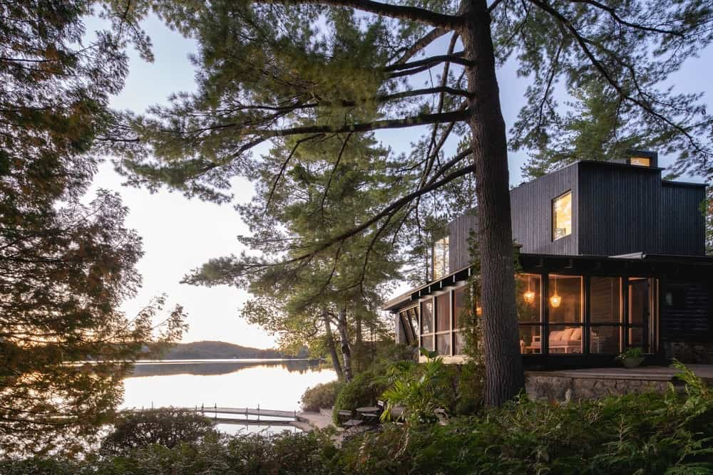This is a view of the cottage with black wooden exterior walls paired with large glass walls facing the landscape.