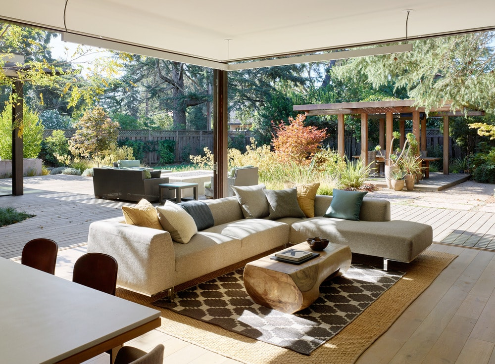 Two entire sides of the living room area is open to the backyard's colorful landscape.