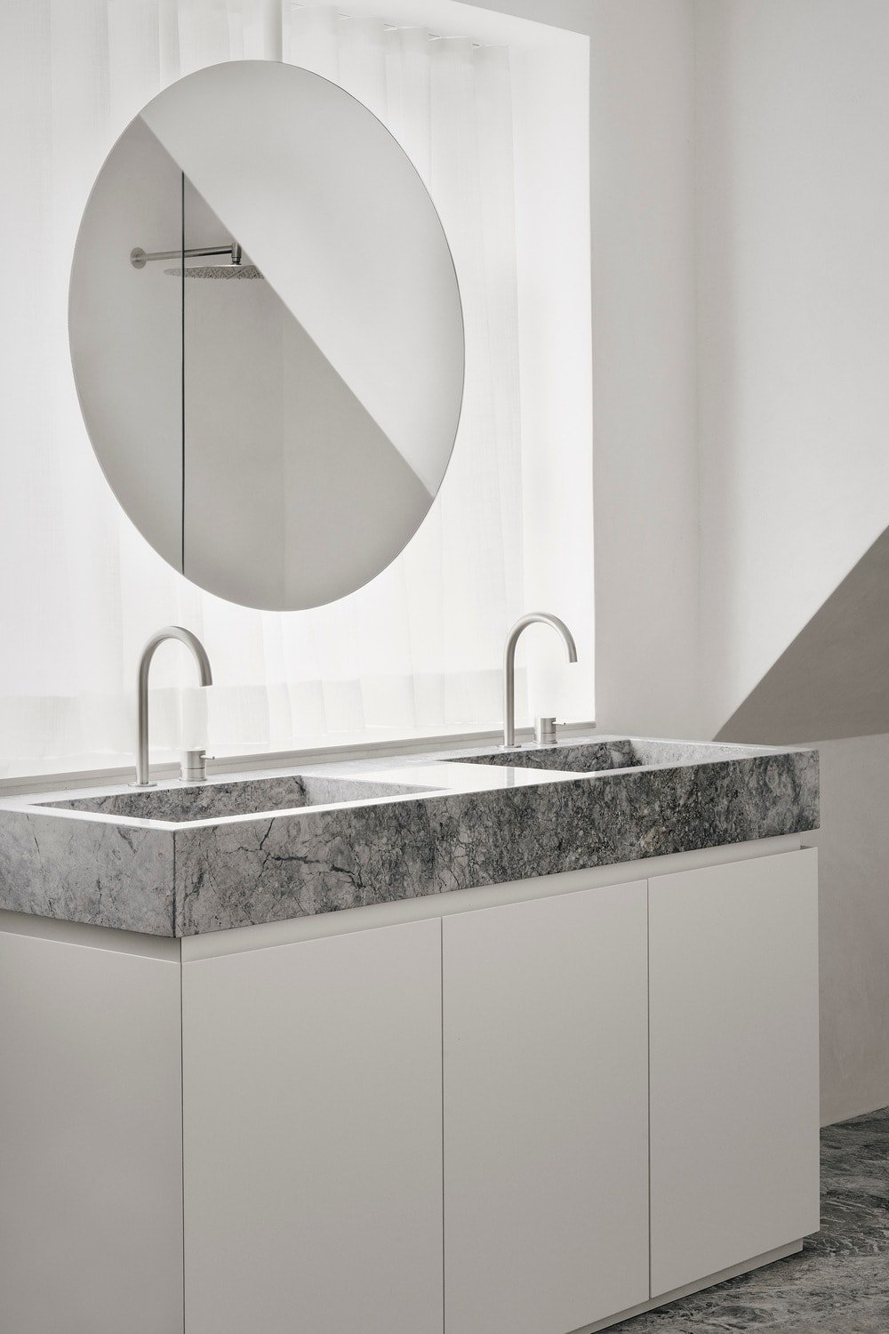 This is a look at the bathroom's two-sink vanity with a gray marble countertop, white cabinetry and a round mirror.