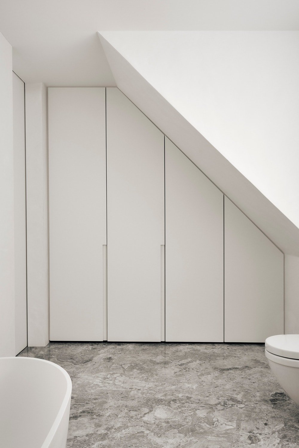 Opposite the shower area is a set of built-in cabinetry that blends well with the white walls.