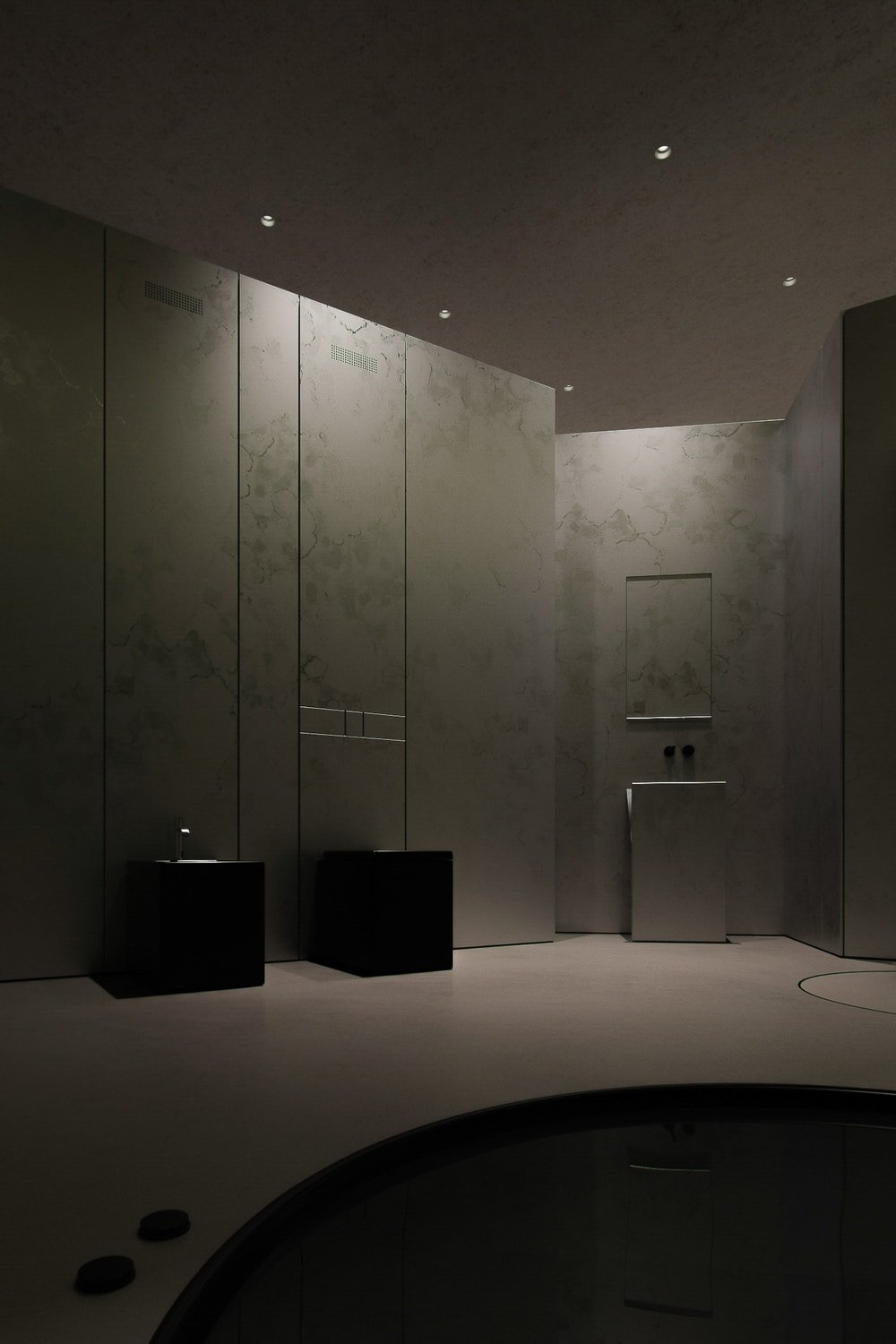 This bathroom has a shower area, sinks and a bathtub embedded onto the floor.