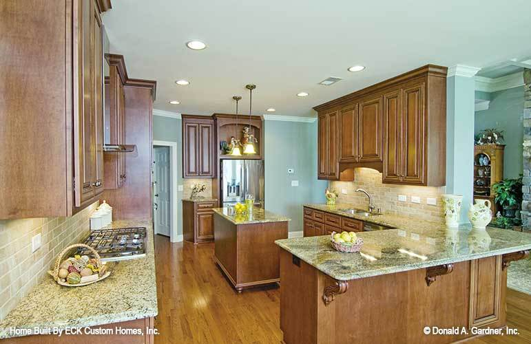 The kitchen is equipped with stainless steel appliances, granite countertops, a double bowl sink, and a small center island.
