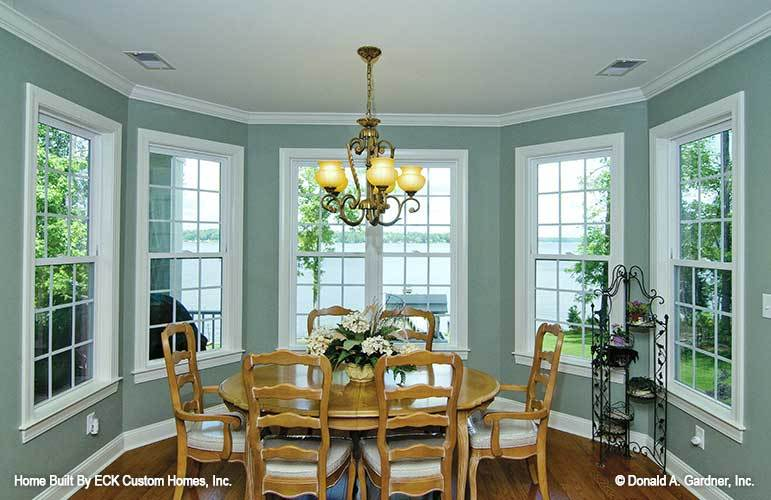 Formal dining room with an ornate chandelier, a round dining set, and a magnificent lake view.