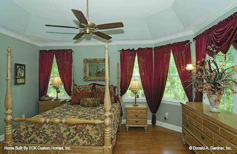 The primary bedroom has natural wood furnishings, a coved ceiling, and white framed windows dressed in classy red drapes and valances.