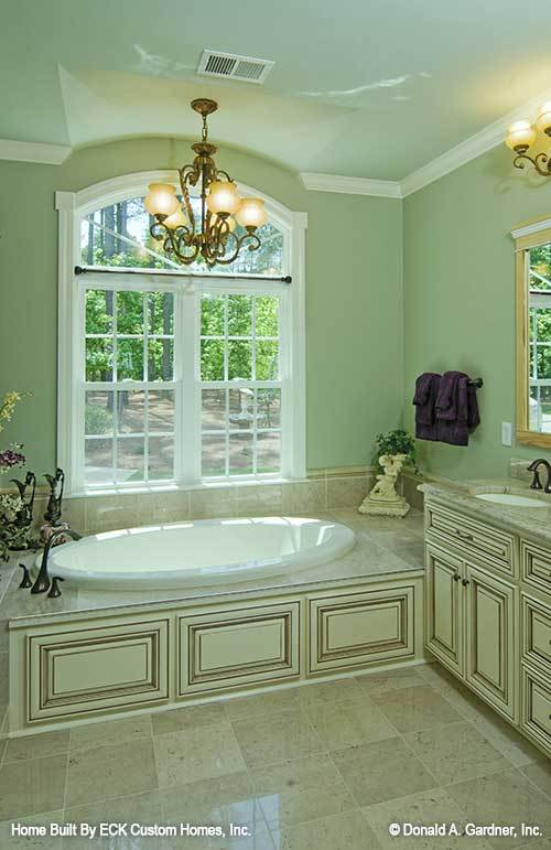 Primary bathroom with a granite top vanity and a drop-in bathtub lighted by a warm glass chandelier.