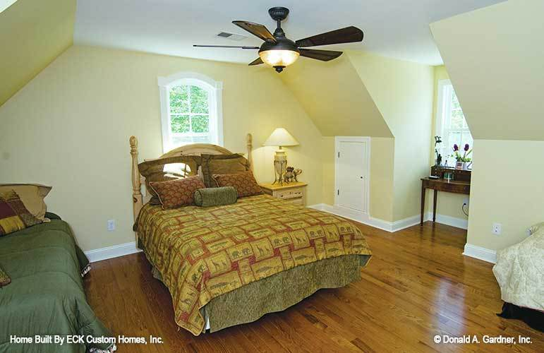 This bedroom offers a dark wood desk and a cozy skirted bed paired with a wooden nightstand.This bedroom offers a dark wood desk and a cozy skirted bed paired with a wooden nightstand.