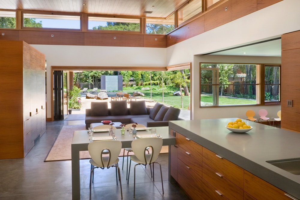 This is a view of the great room that houses the living room and kitchen. The living room has a large L-shaped sofa while the kitchen has a large L-shaped kitchen island with its attached table.