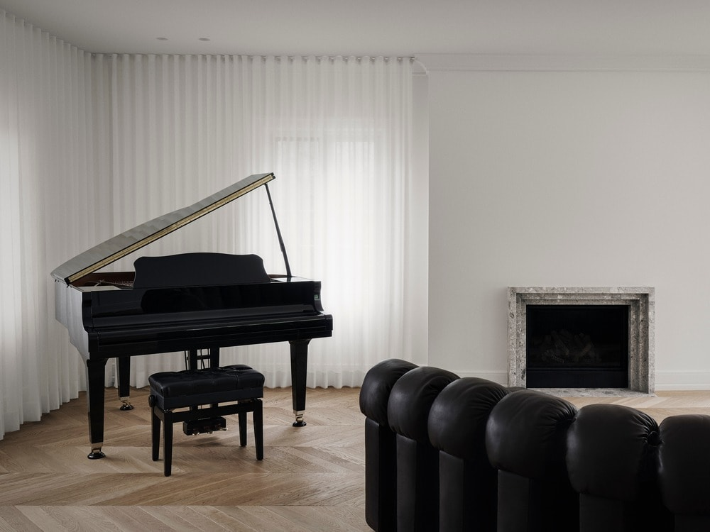 This is a look at the living room area with a black grand piano at the corner standing out against the bright walls and curtained windows.