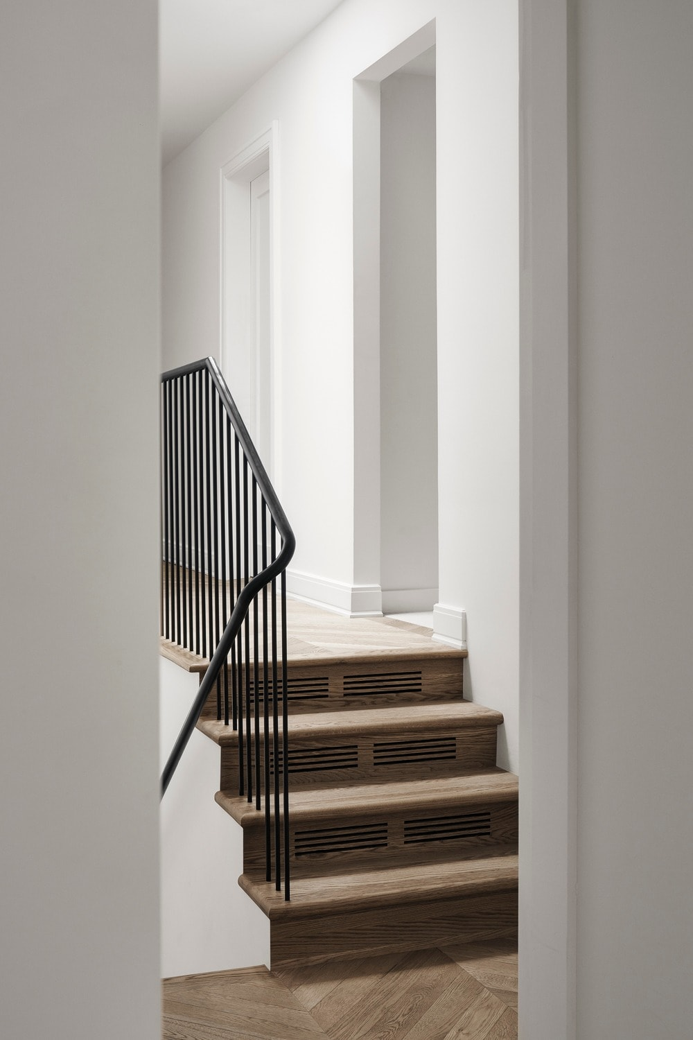 The staircase has black wrought iron railings that stand out against the white walls.