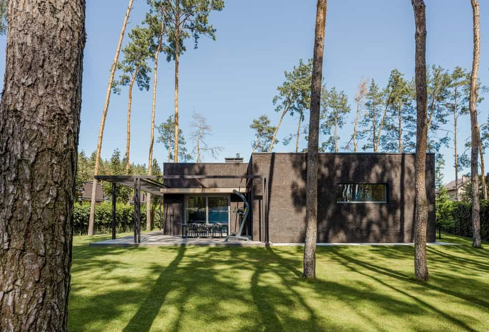 This is a view of the house from the grass lawn. You can see here the dark earthy tone of the house exterior that matches well with the trees and contrasted by the grass lawn.