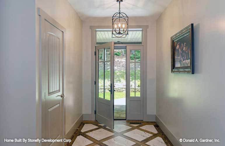 The foyer has a white entry door, candle chandeliers, and a framed painting adorning the gray walls.