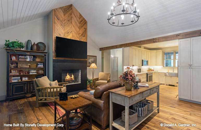 Sitting on the left side of the living room is the kitchen lined with a rustic beam.