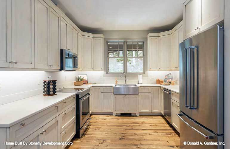 The kitchen is equipped with slate appliances, a farmhouse sink, white cabinets, and quartz countertops.