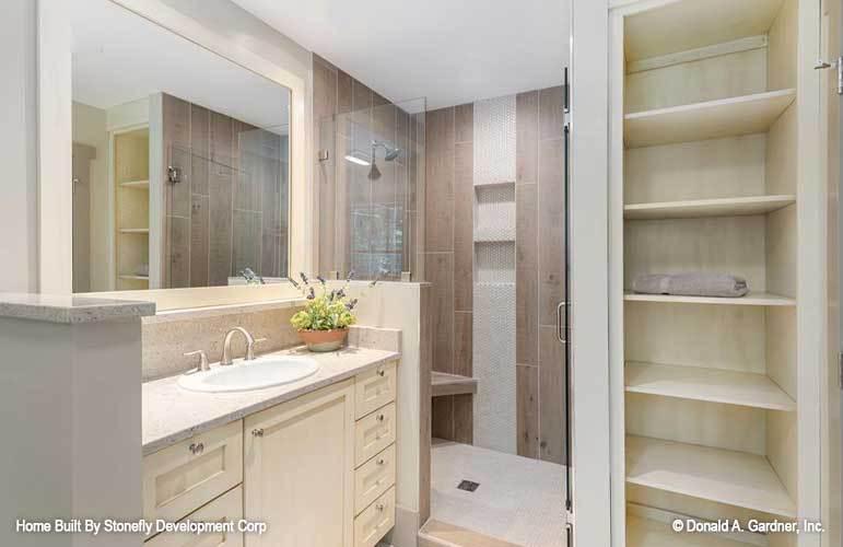 Primary bathroom with linen storage, walk-in shower, and sink vanity.